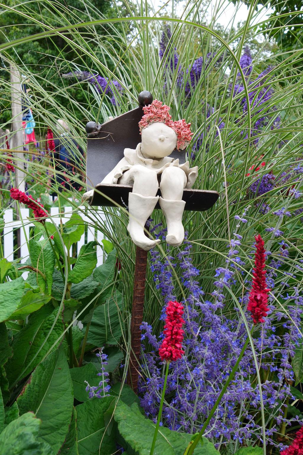 i Trädgården -keramikflicka sitter i rabatten, dekoration